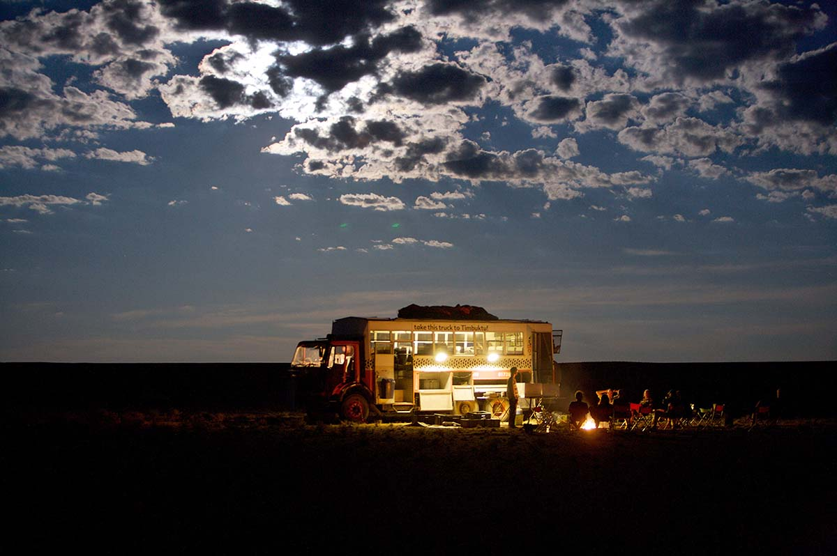 A group sits around a campfire beside and overlanding truck at night