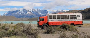 Dragoman Overland truck parked besides a lake with mountains in the background