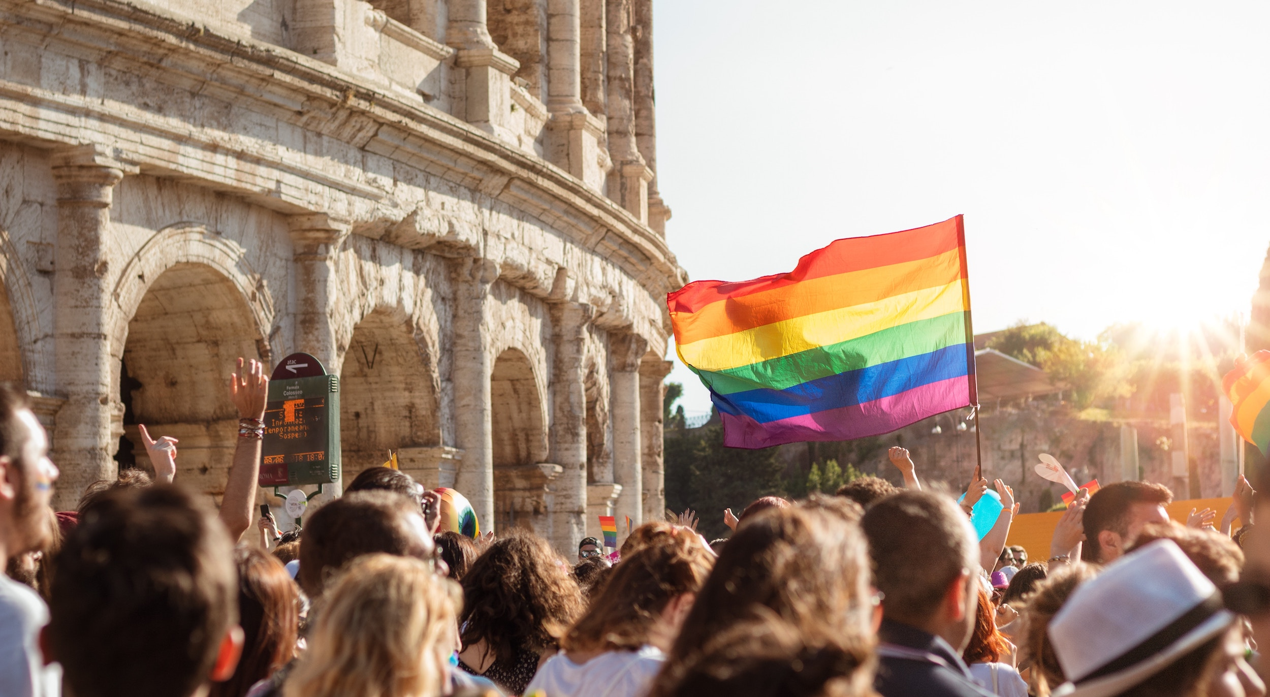 Group of people in Rome, Italy walking with rainbow Pride flag