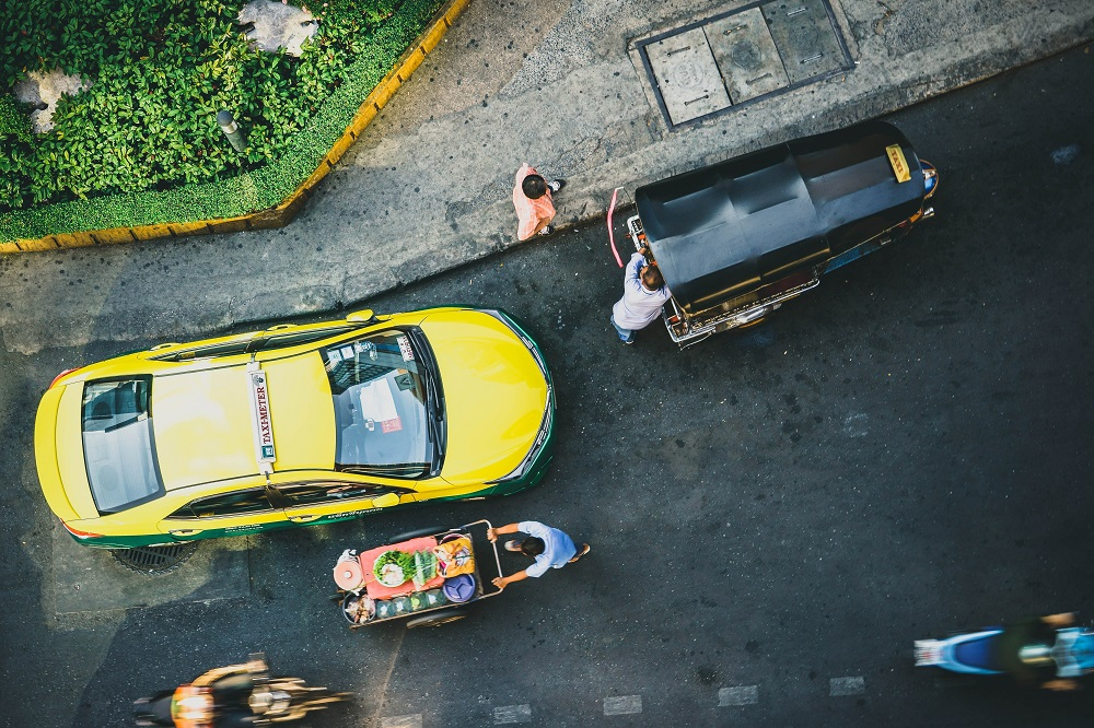 Birds eye view of a street in Bangkok with cars and motorbikes moving quickly