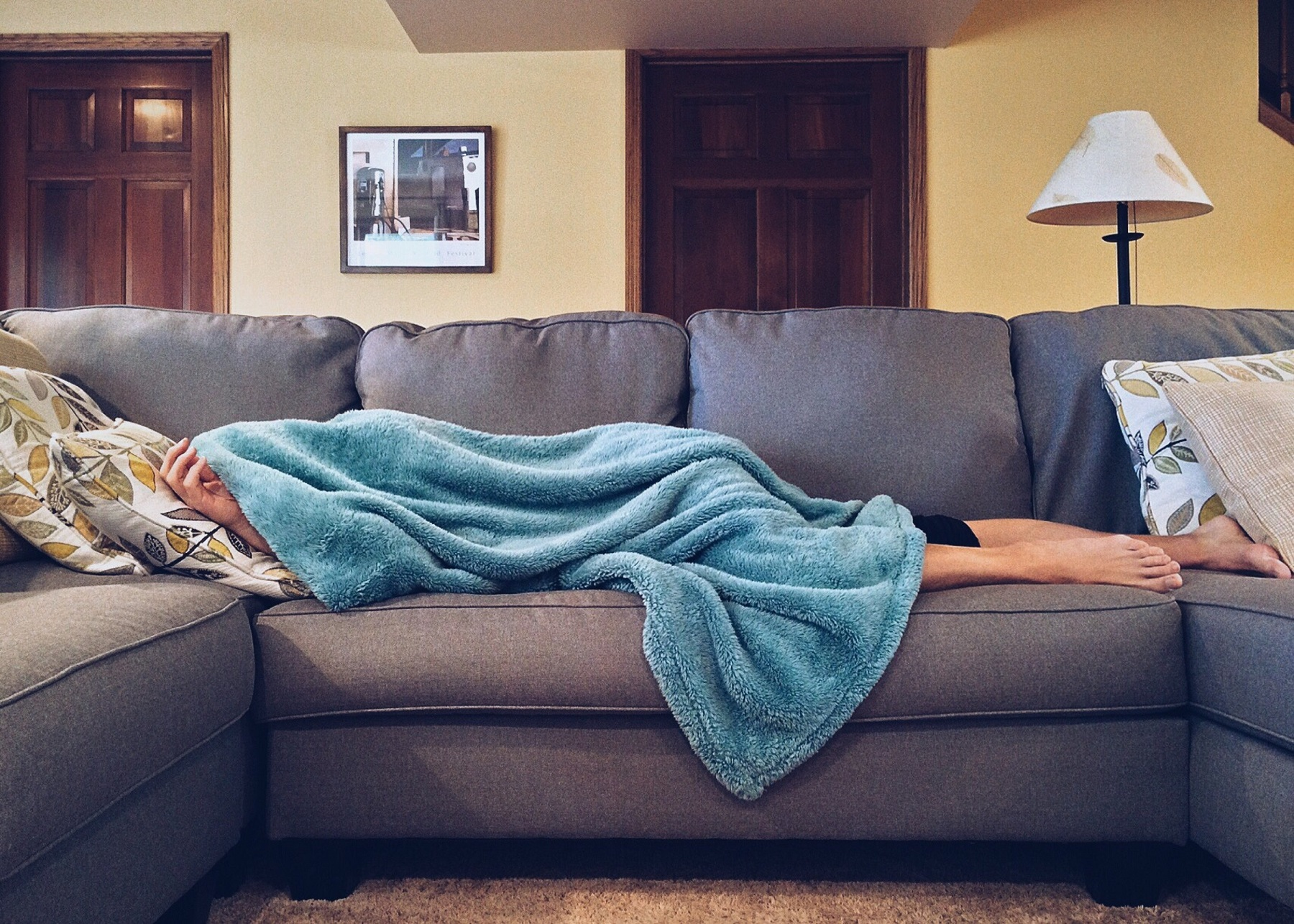 Person sick with flu lying on the sofa under a blanket