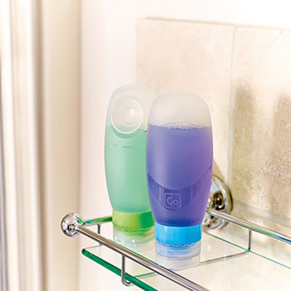 Squeezy bottles with toiletries inside on a shelf in a shower