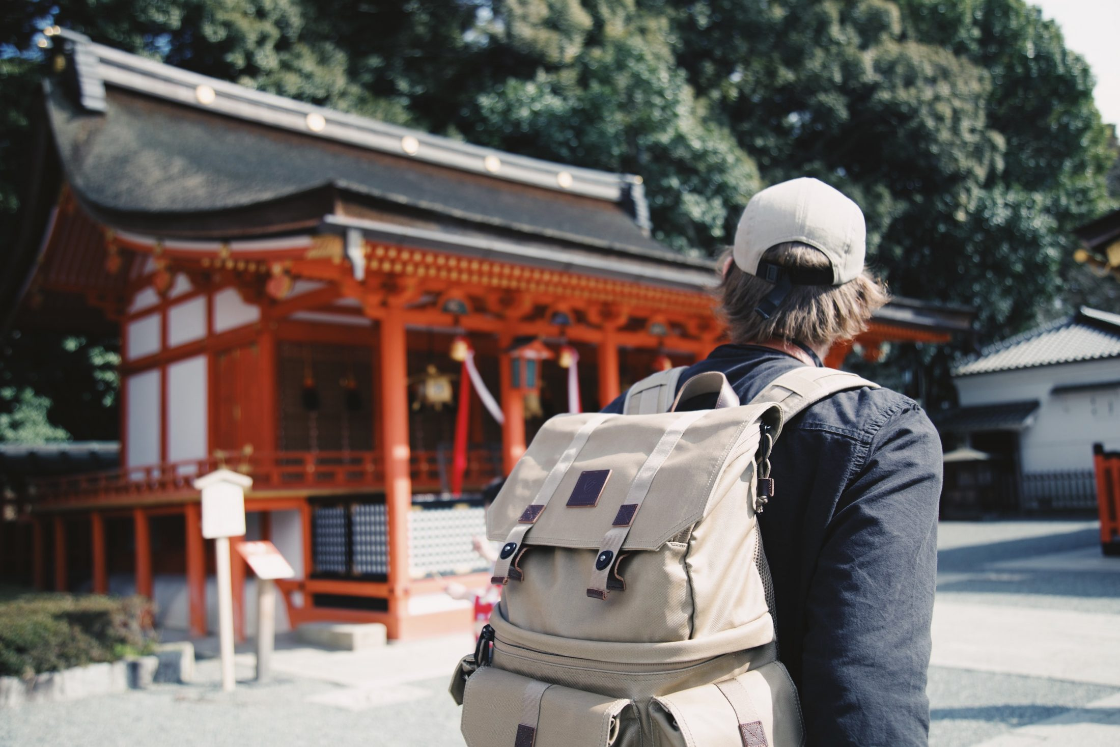 A man standing alone in front of a traditional building in Asia