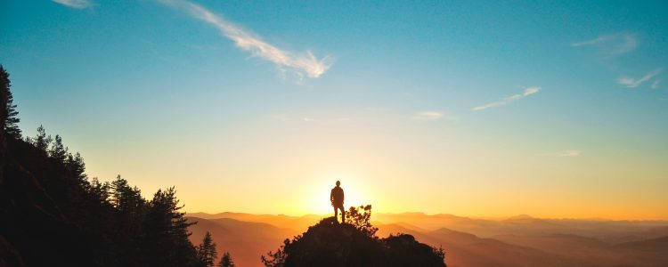 Person standing on top of rocks looking at the sunset