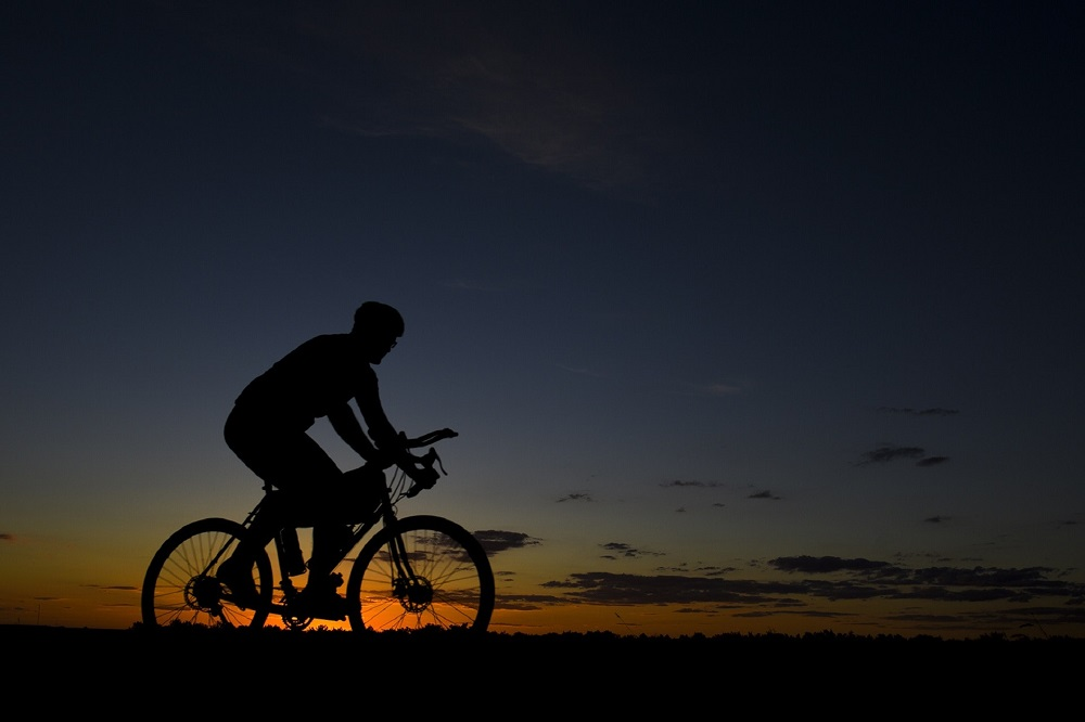 Man cycling at sunset