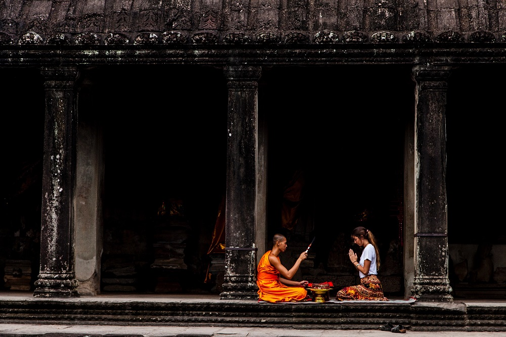 Western woman sitting praying with an buddhist monk