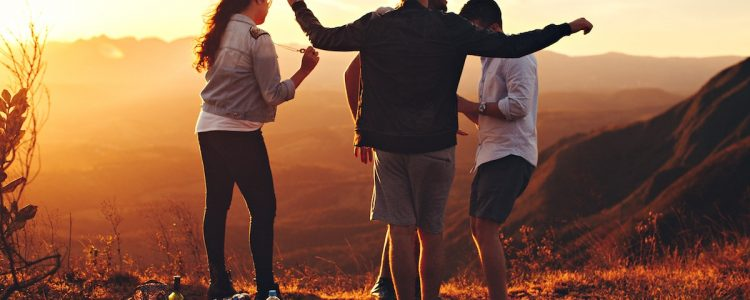 Group of friends at sunset on a hillside