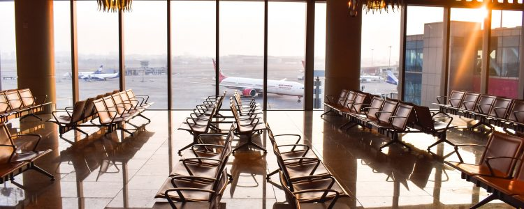 An airport waiting area with decorative lighting and large windows looking over planes
