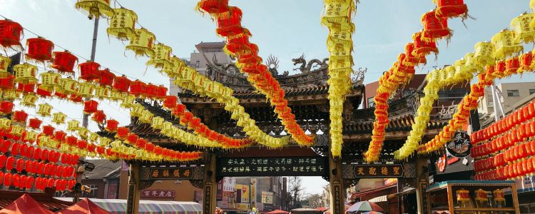 Busy street suring a Chinese festival with lanterns strung above the crowd