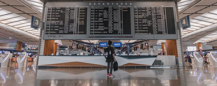 A person looks at an airport departures board