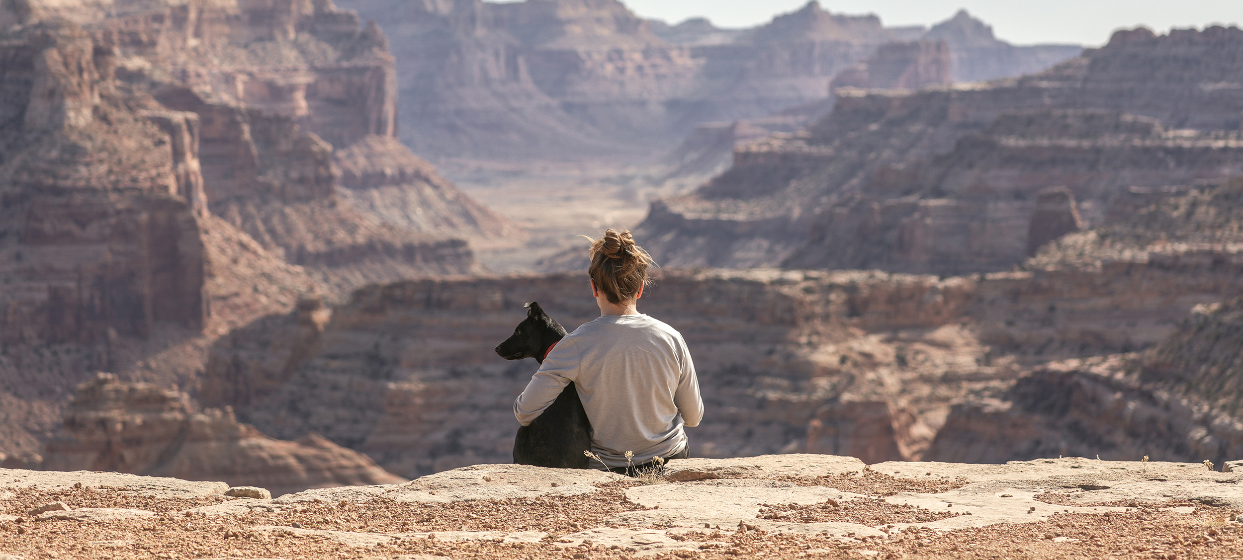 Woman sitting with dog aove a canyon