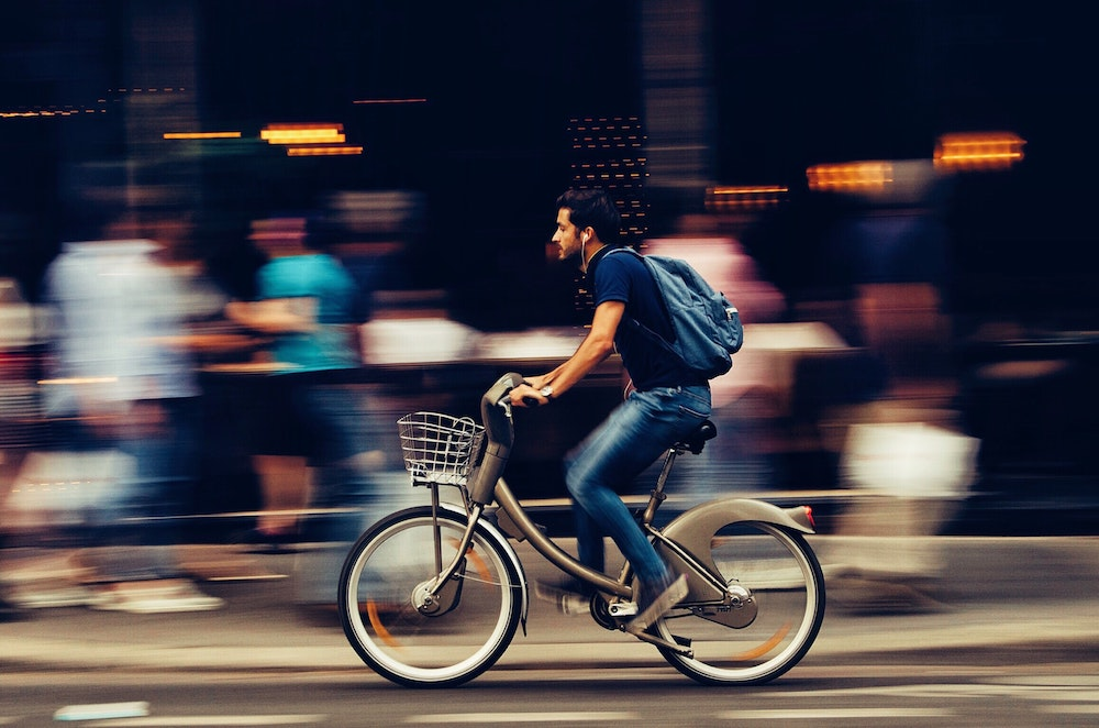 Man cycling quickly on a busy street in Asia