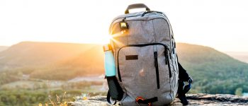 Backpack and water bottle with a sunset behind