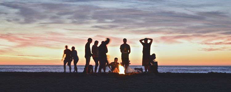 People around a fire on a beach at sunset