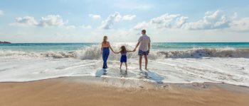 Man, woman and child hold hands standing in the surf on a beach