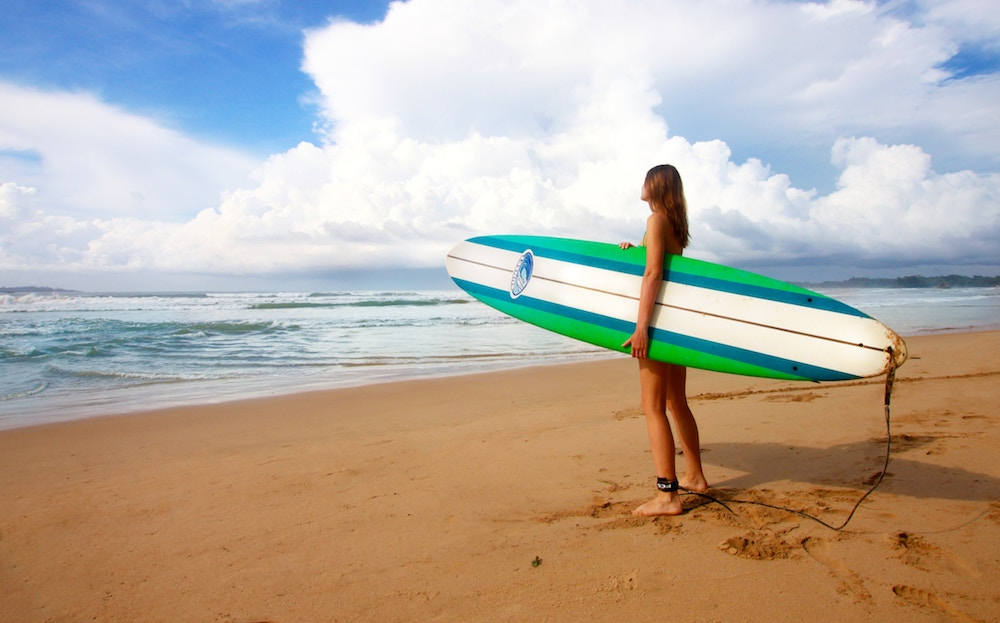 Girl with a surf board on a beach in Sri Lanka